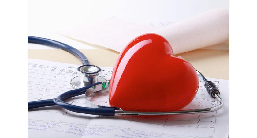 czerwone serce z tworzywa i słuchawki lekarskie leżące na dokumentach