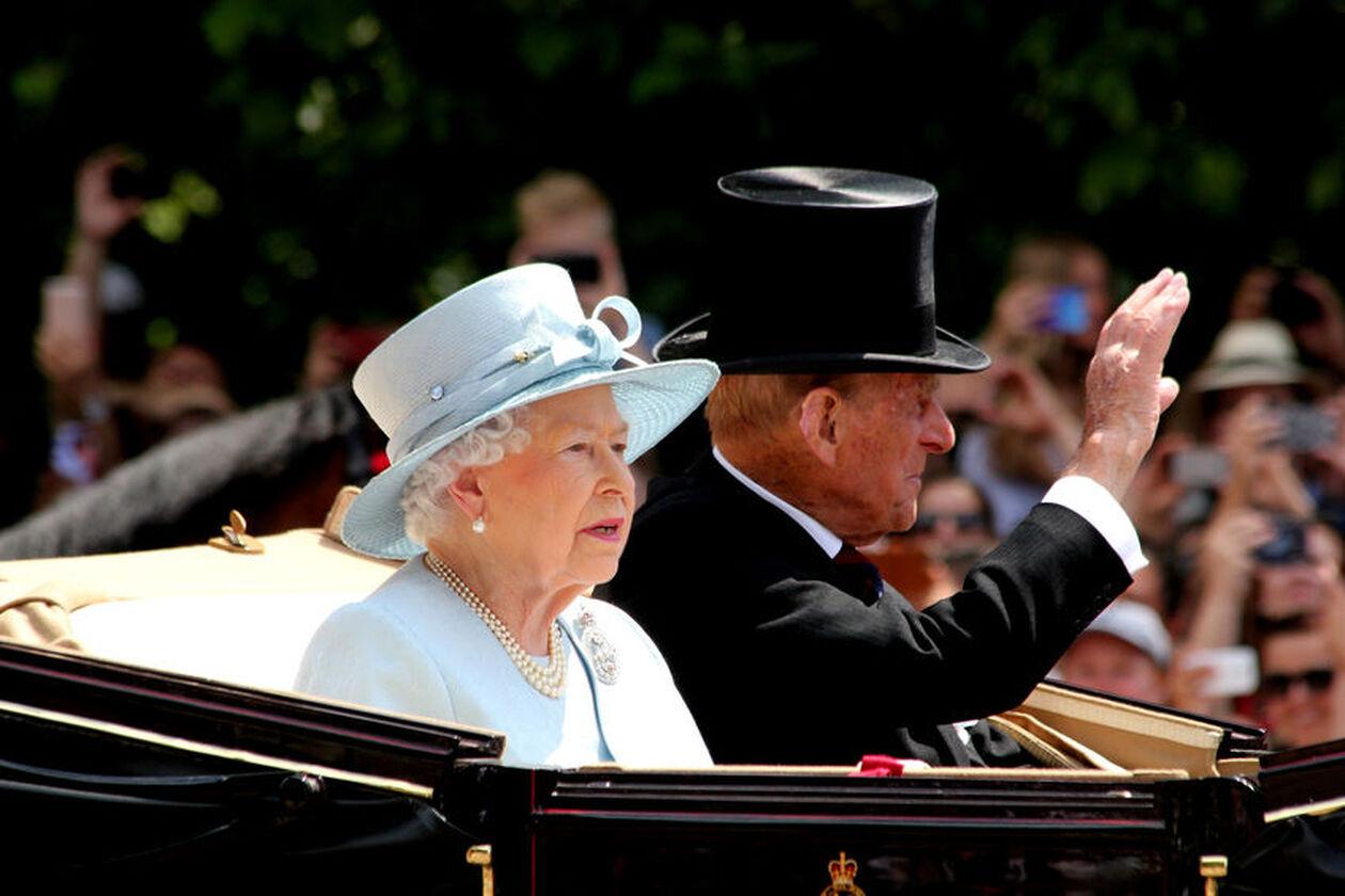 Królowa Elżbieta II w białym stroju siedząca w powozie