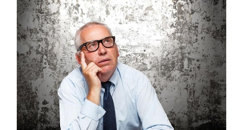 starszy mężczyzna w okularach zastanawia się i podpiera ręką twarz