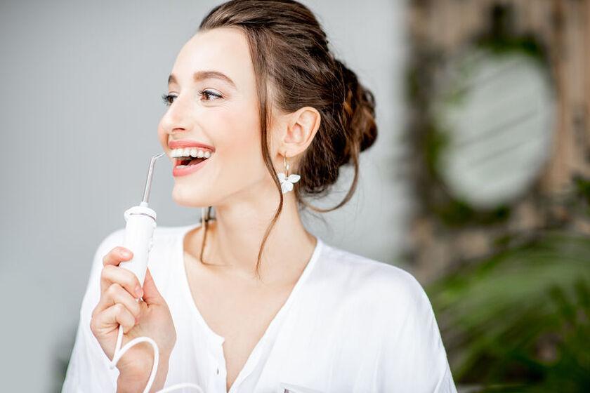 Kobieta używa stacjonarnego irygatora do zębów
