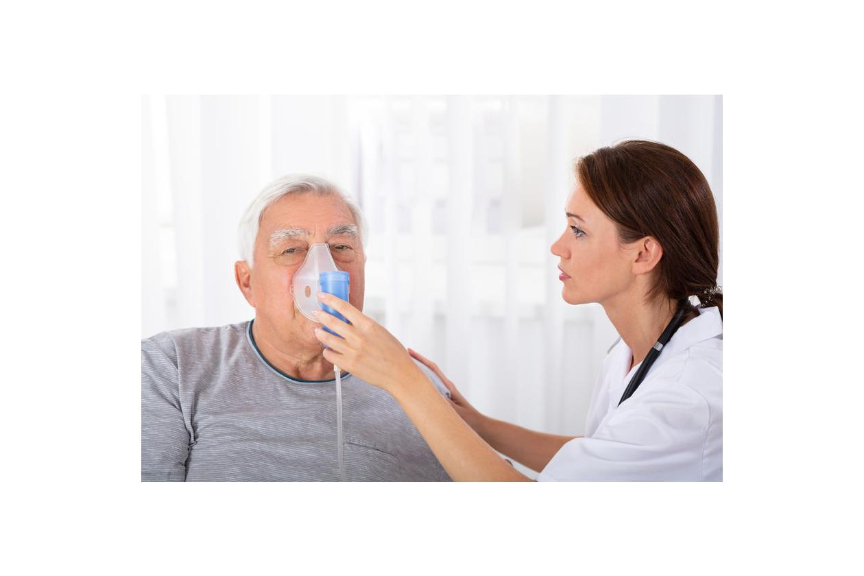 Pielęgniarka pomaga choremu w przeprowadzeniu biernej tlenoterapii