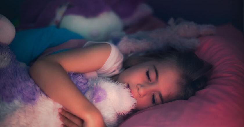 Dziewczynka bawi się zabawką w czasie snu