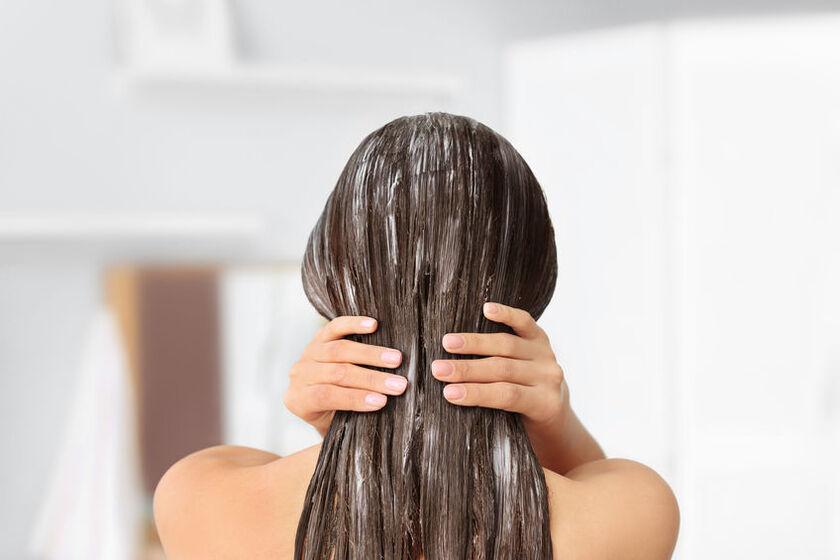Kobieta stosuje emolienty na włosy