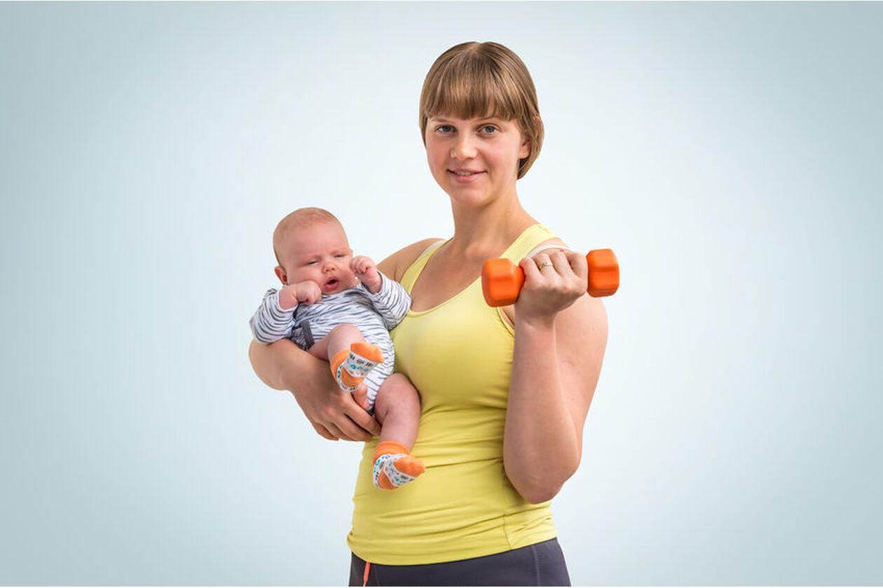 Kobieta wykonuje ćwiczenia po porodzie z niemowlakiem na rękach