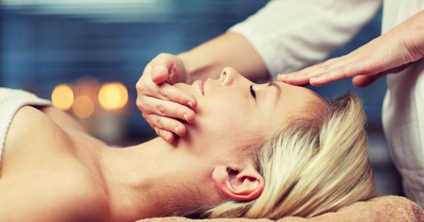 Kobieta ma wykonywany masaż twarzy w salonie SPA