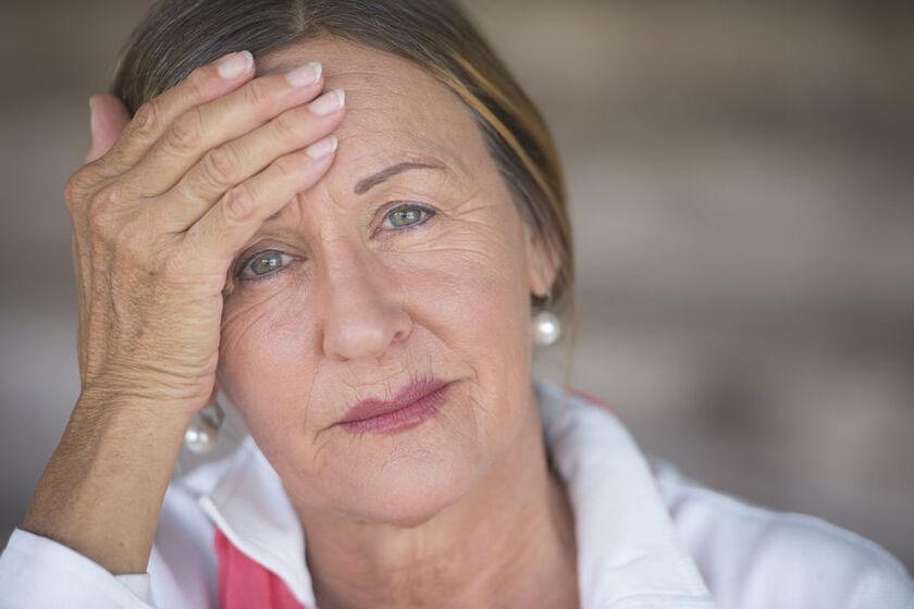 Dojrzała kobieta odczuwa ból głowy w  przebiegu menopauzy