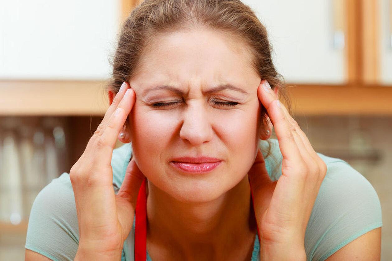 Kobieta odczuwa napięciowy ból głowy