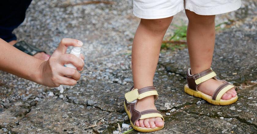 Mama spryskuje nogę dziecka repelentem na komary