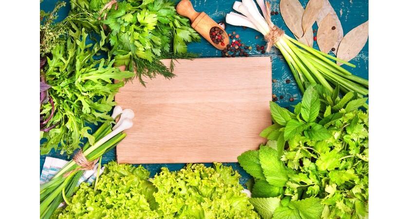 Zioła i zielone rośliny wokół drewnianej deski