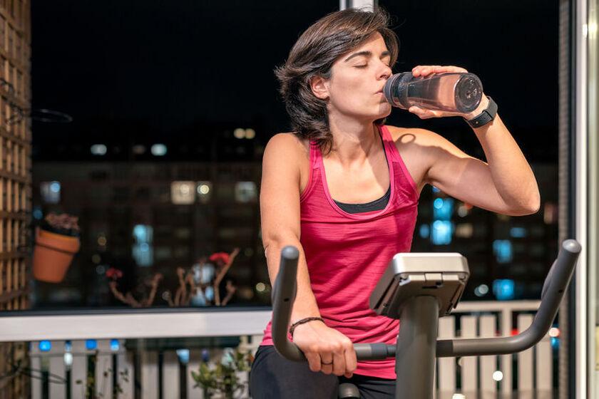 Kobieta pije elektrolity w trakcie ćwiczeń na siłowni