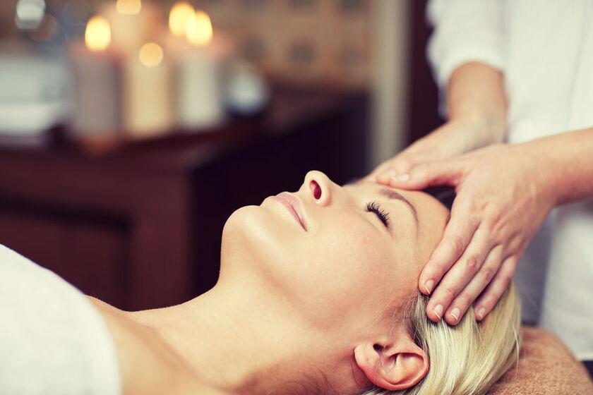 Kobieta w trakcie masażuskóry głowy w gabinecie SPA