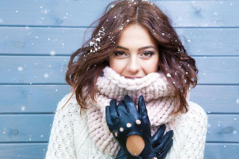 Kobieta ogrzewa dłonie rękawiczkami