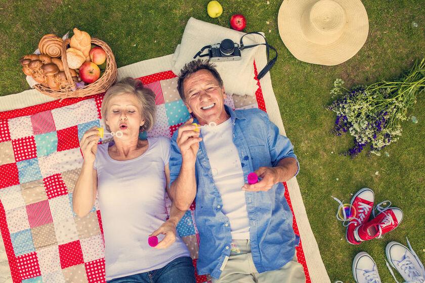 Para dojrzałych ludzi leżąca na piknikowym kocu