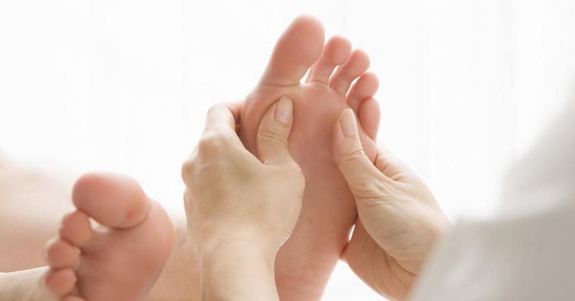 Kobieta w trakcie zabiegu akupresury stopy