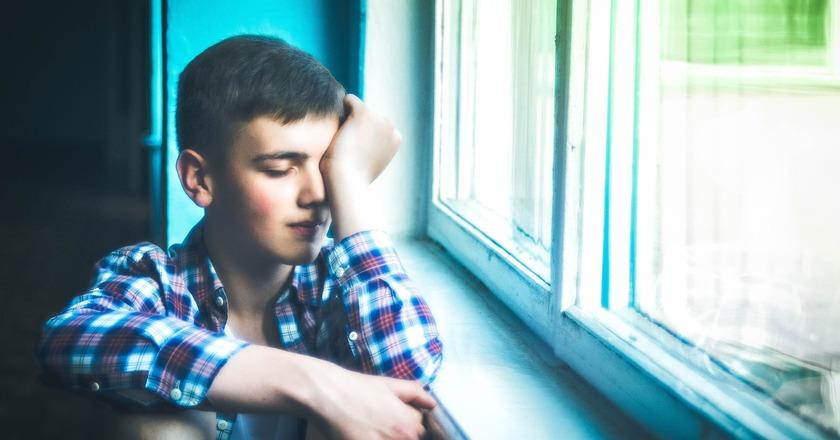 Smutny chłopiec siedzący w oknie