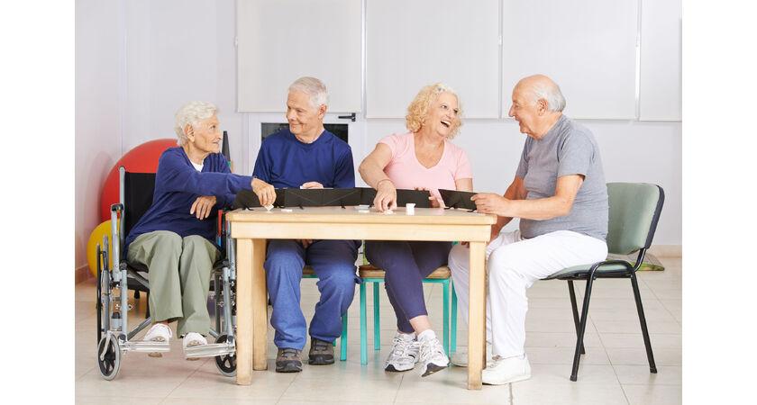 Seniorzy przy stolę grają w grę towarzyską