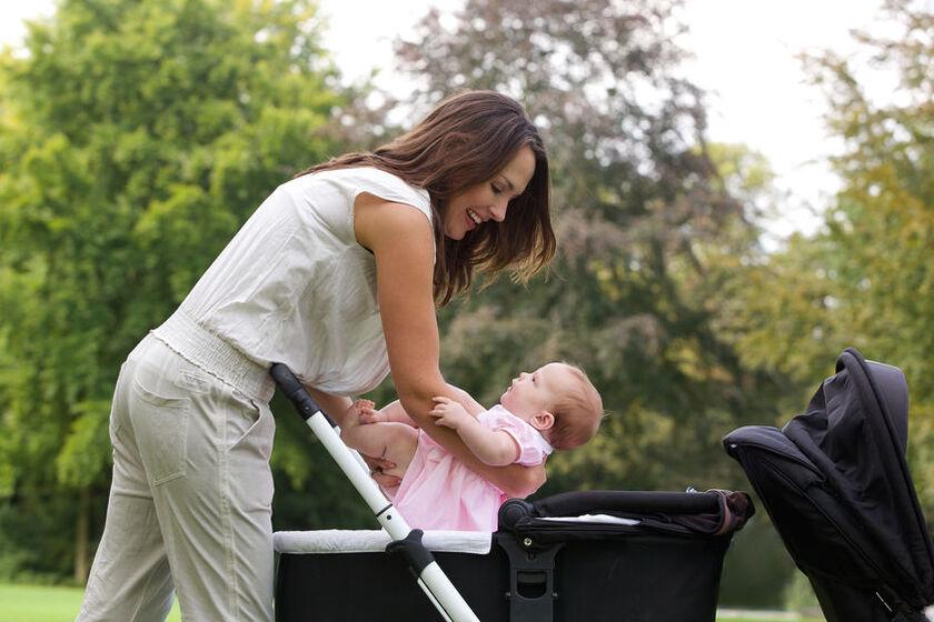 Mama wkłada niemowlaka dla wózka