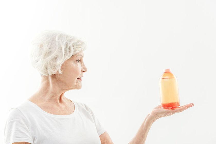 Starsza kobieta trzyma szampon na wypadanie włosów