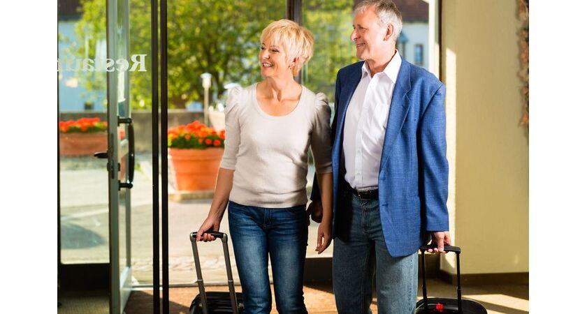 Kobieta i mężczyzna z walizkami wchodzą do hotelu