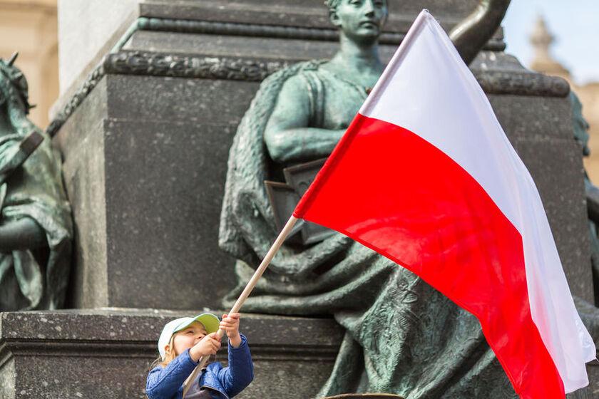 Dziecko trzyma w rękach flagę Polski