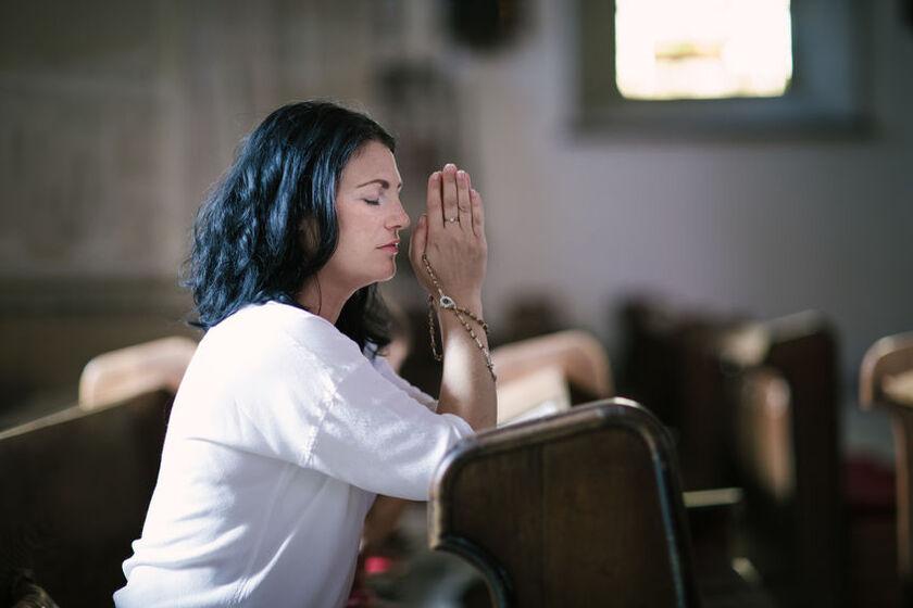 Kobieta odmawia różaniec w kościele