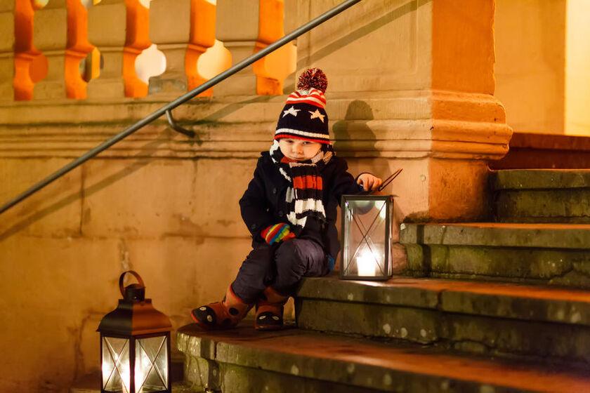 Chłopiec z lampionem na kościelnych schodach