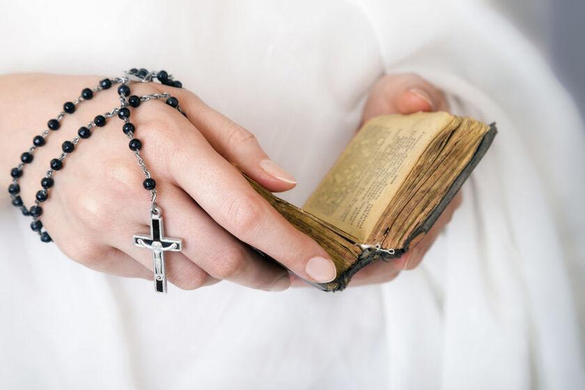 Kobieta trzyma w jednej dłoni różaniec a w drugiej katechizm