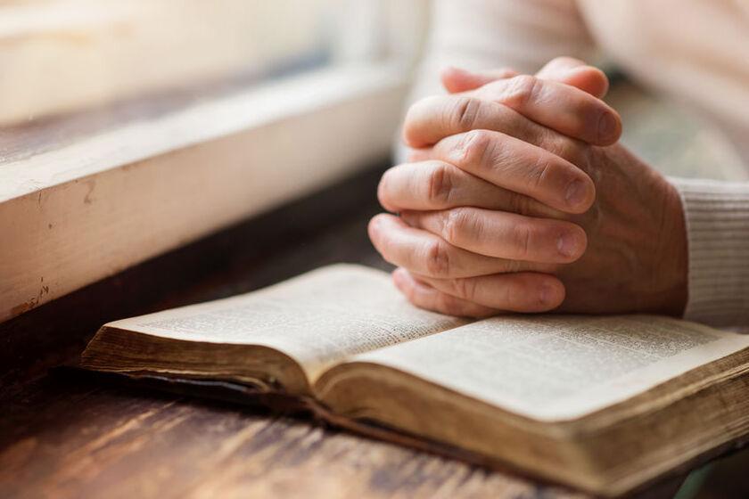 Kobieta modli się przy oknie
