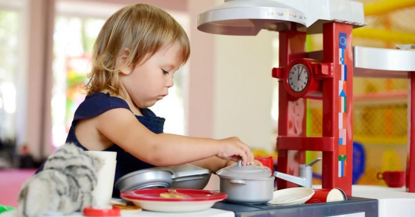 Trzyletnia dziewczynka bawi się zabawkowąkuchnią