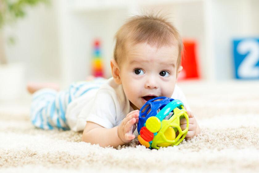 Półroczne dziecko bawi sięzabawką