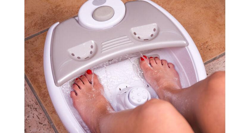 Kobieta używa masażera wodnego do stóp