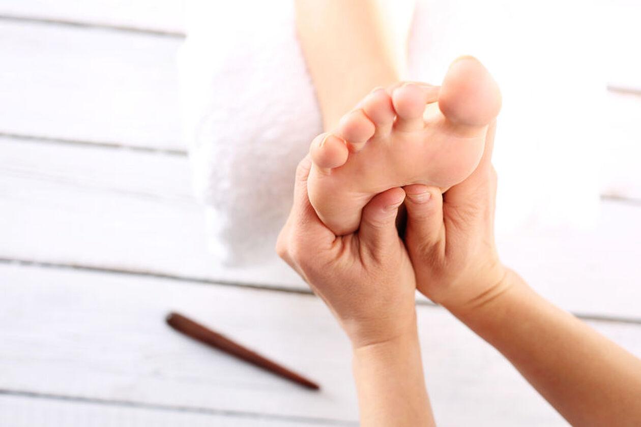 Kosmetyczka uciska receptory na stopach