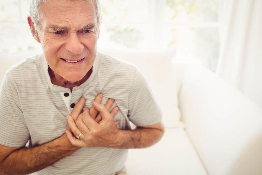 Starszy mężczyzna trzyma sięza serce
