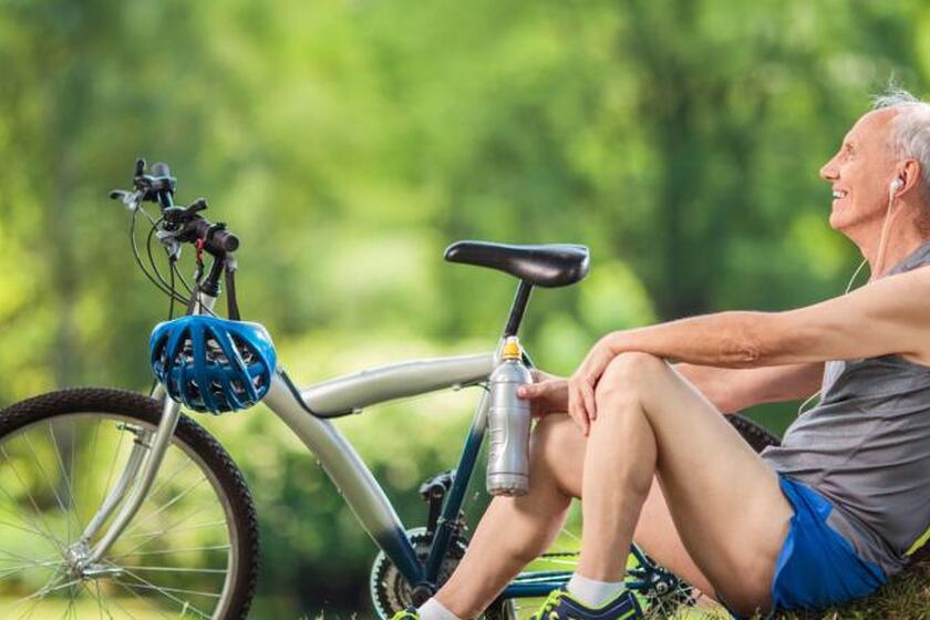 Mężczyzna odpoczywa pod drzewem po jeździe na rowerze