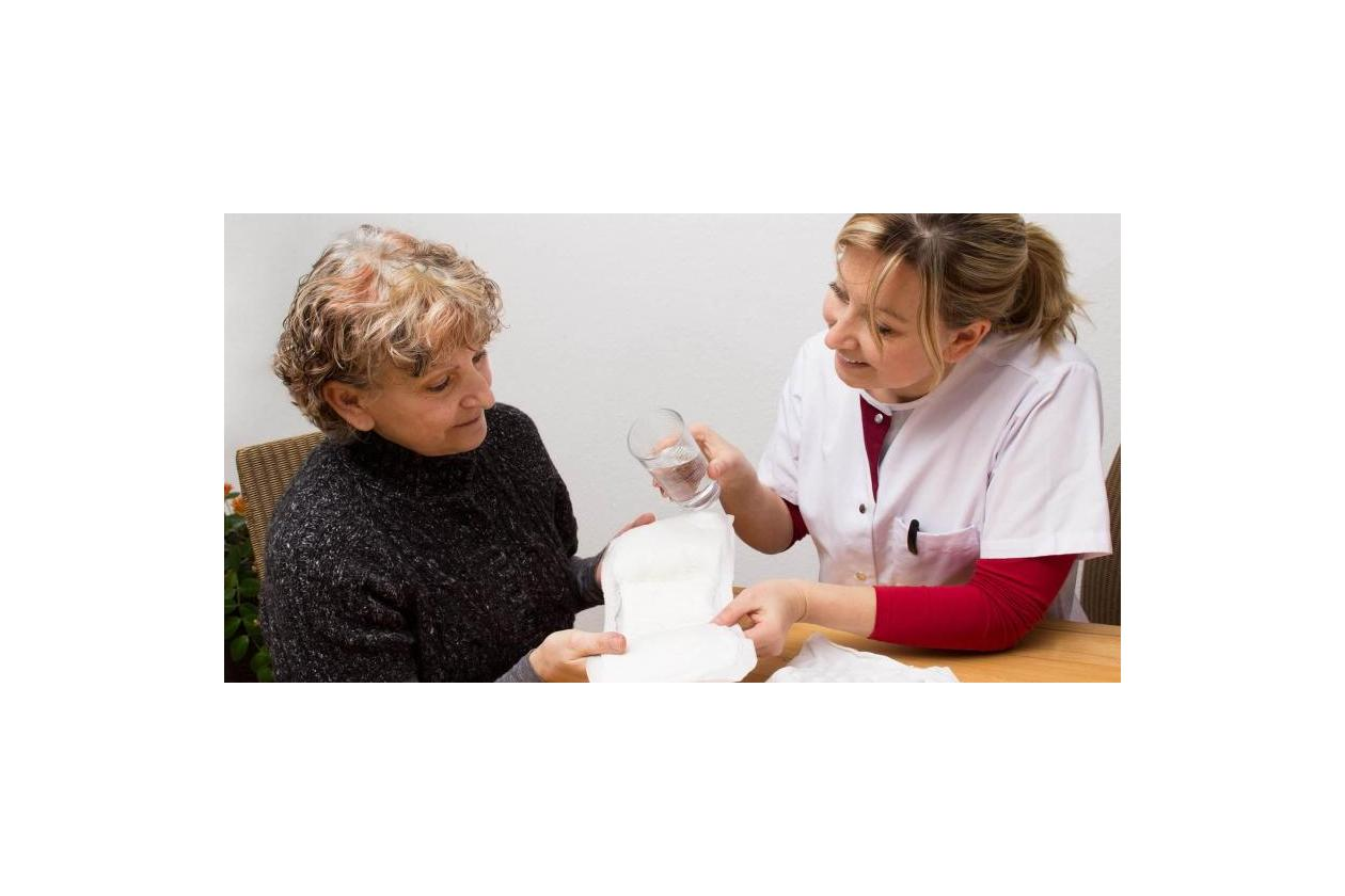Lekarka pokazuje kobiecie wkładki urologiczne na nietrzymanie moczu