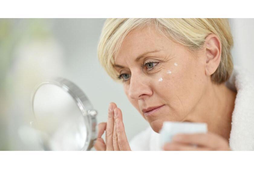 Dojrzała kobieta smaruje twarz kremem, przeglądając się w lusterku