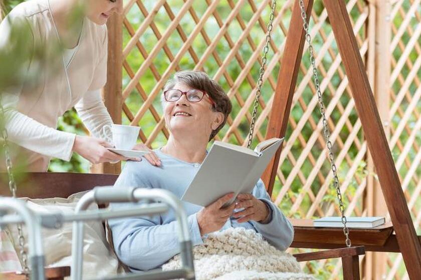 Kobieta podaje drugiej siedzącej na huśtawce filiżankę z herbatą