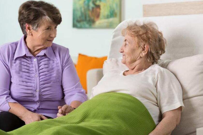 Kobieta siedzi przy łóżku chorej