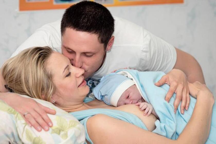 Kobieta trzyma noworodka, mężczyzna ją całuje