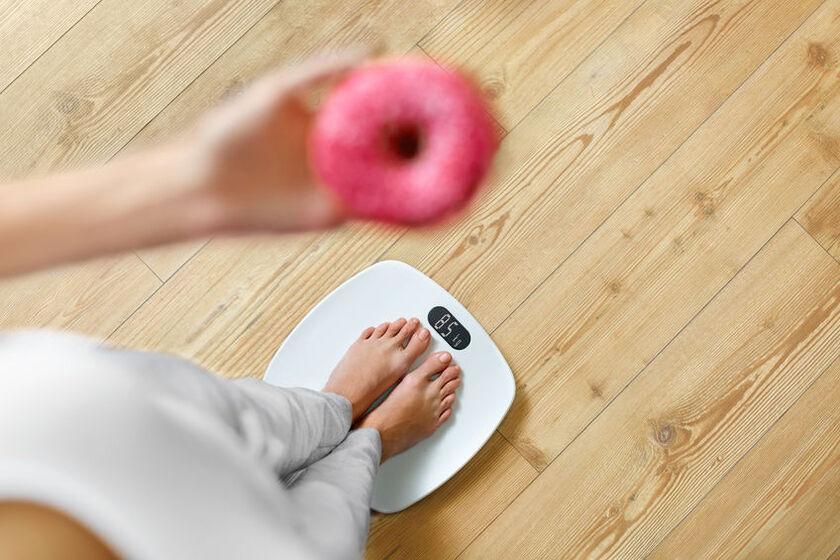 Kobieta z pączkiem w ręki stoi na wadze elektronicznej