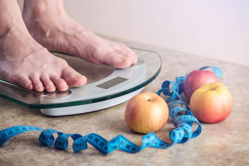 Mężczyzna stoi na wadze łazienkowej z pomiarem tkanki tłuszczowej