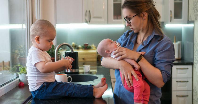 Kobieta trzyma na rękach dziecko ze smoczkiem w buzi