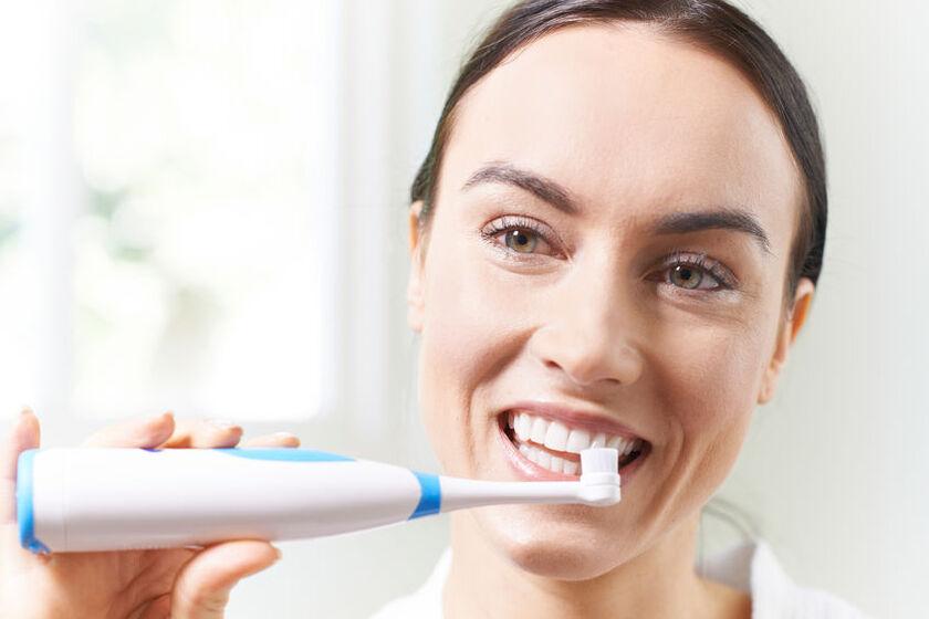 Kobieta myje zęby szczoteczką elektryczną z czujnikiem nacisku