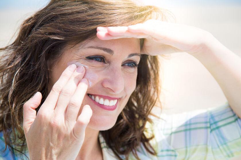 Kobieta smaruje twarz krem z filtrem
