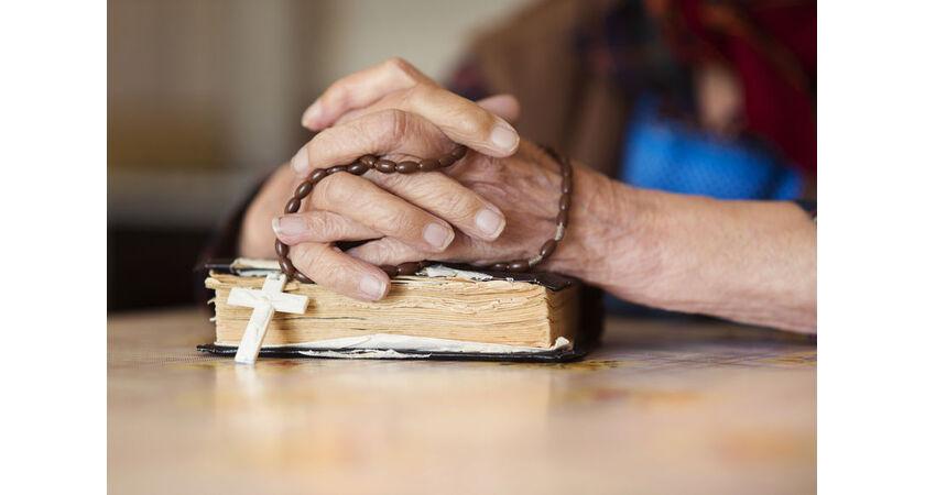 Starsza kobieta odmawia modlitwęróżańcową