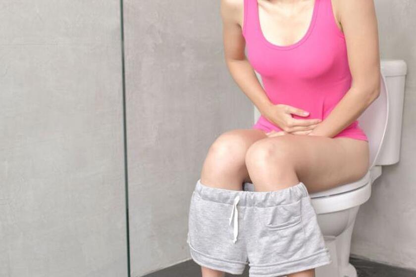 Kobieta siedząca na toalecie trzymająca się za brzuch