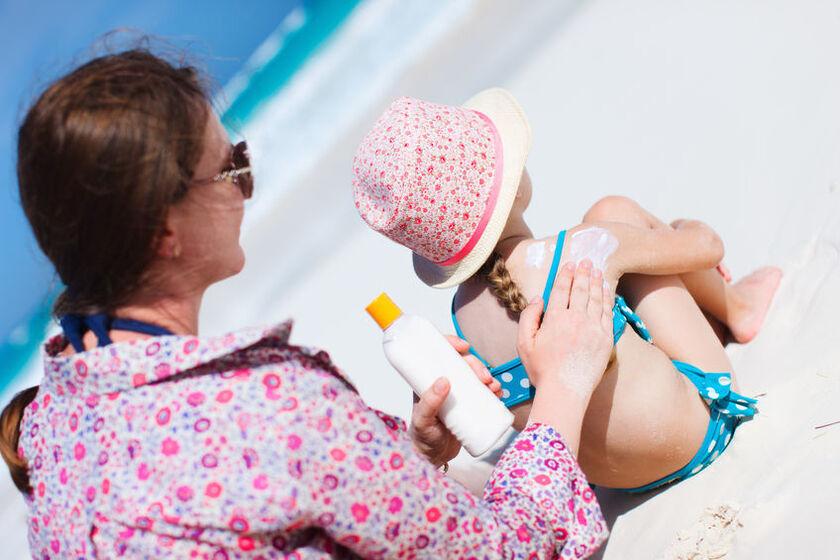 Kobieta smaruje dziecko balsamem do opalania 50