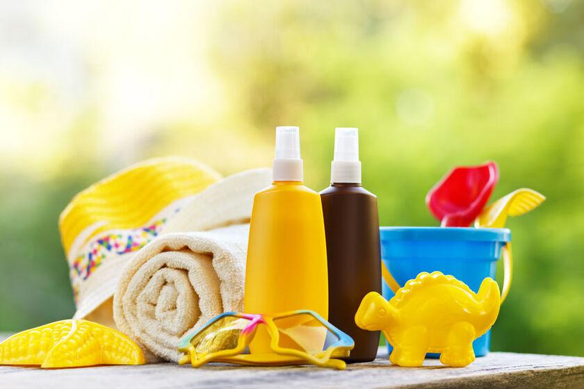 Kosmetyki do opalania, ręcznik i kapelusz