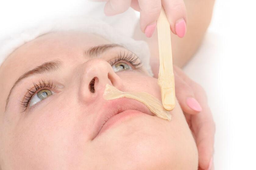 Kobieta w trakcie zabiegu depilacji twarzy kremem