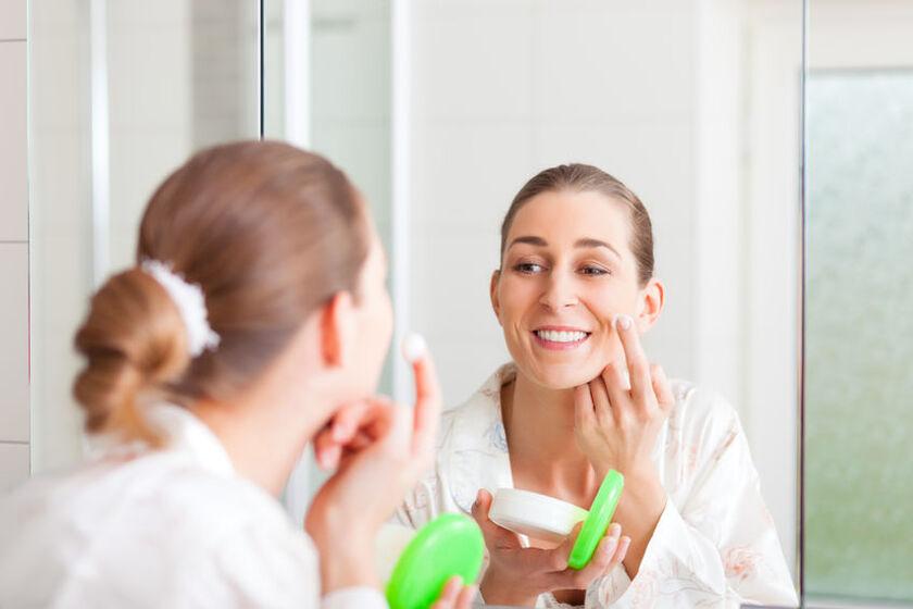 Kobieta smaruje się kremem z filtrem pod makijaż